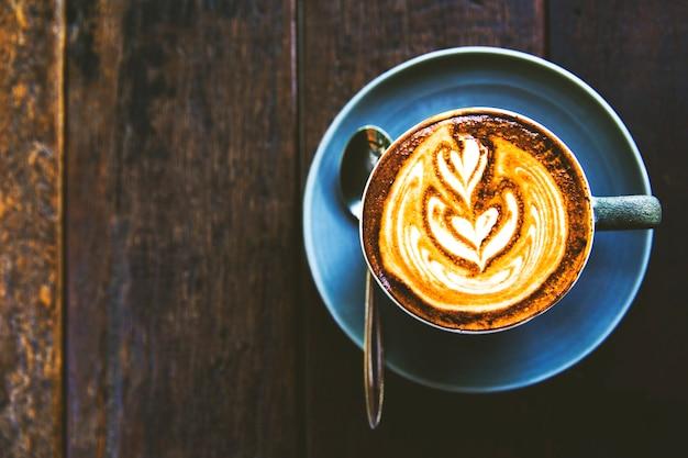 Чашка горячего капучино на деревянном столе