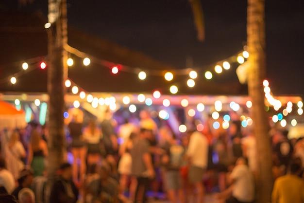 オーシャンビューのスイミングプールに閉じた友人と夕暮れ時のビーチパーティー。