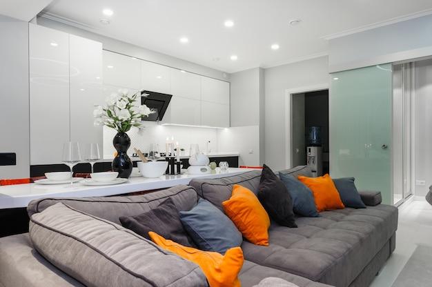 Современная белая гостиная с открытой дверью спальни