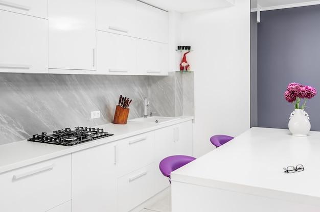 ダイニングテーブルと紫の椅子を備えたモダンなキッチン
