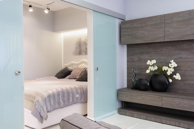 寝室のドアが開いているモダンな白いリビングスタジオ