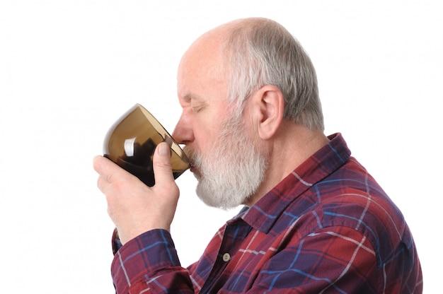 カップから飲む年配の男性。