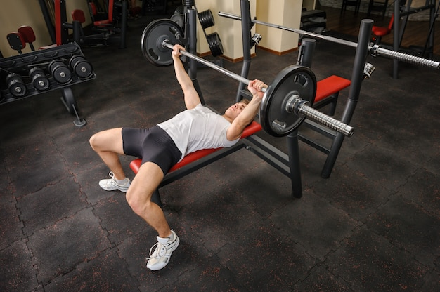 Молодой человек делает тренировки жим в тренажерном зале