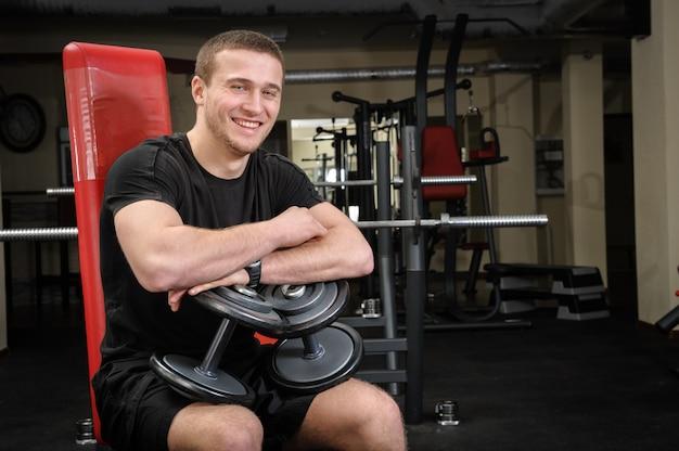 Молодой человек сидит после тренировки в тренажерном зале