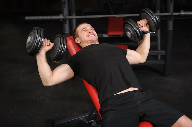 Молодой человек делает тренировки жим гантелей наклона в спортзале