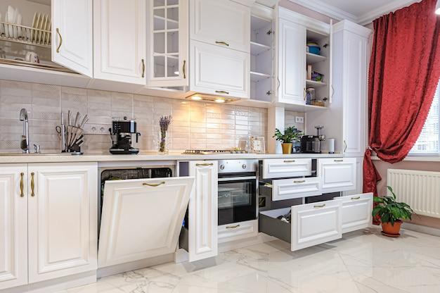 開いたドアと引き出し付きの豪華なモダンな白いキッチンインテリア