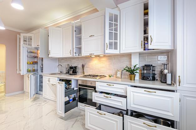 開いたドアと引き出し付きのモダンな白いキッチンインテリア