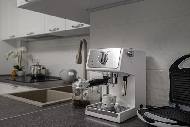 Маленькая кофеварка эспрессо и жаровня в современном минималистичном интерьере белой кухни