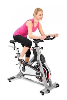Молодая женщина делает упражнения на велосипедах
