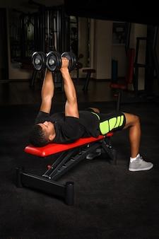 腕のベンチをしている若い男がジムでトレーニングを飛ぶ