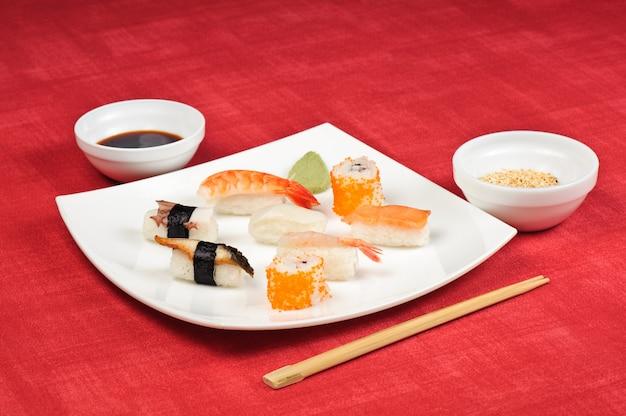 白い正方形のプレートで横になっている寿司盛り合わせ