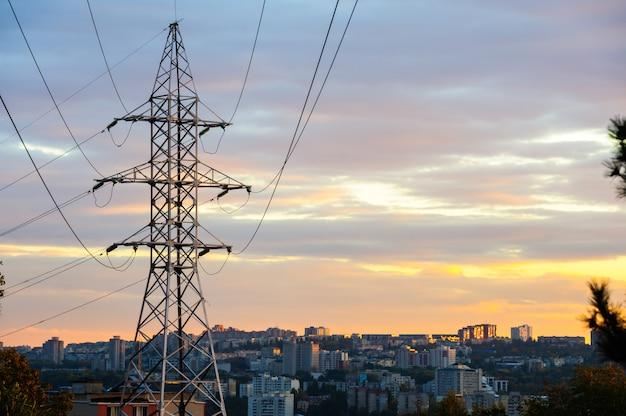 曇りの夕日に電気の鉄塔と電力線のシルエット。