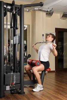 ラッツプルダウントレーニングを行う若い男