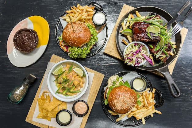 Бургерсм картофель фри, севиче, ребрышки и маффин на деревянном столе