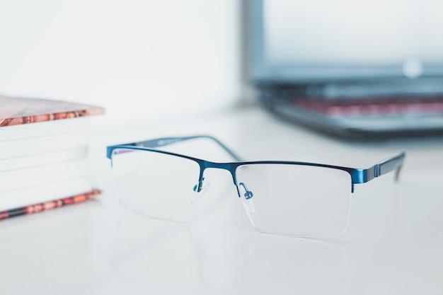 本とノートパソコンのメガネ