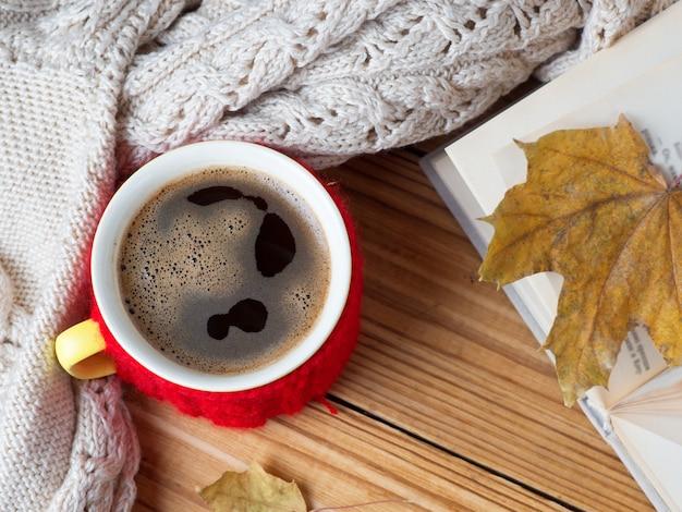 Кружка горячего кофе с теплым зимним свитером и книга на столе. зимняя композиция