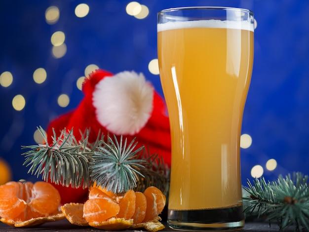 Бокал праздничного рождественского пива ремесло на синем. празднование вечеринки