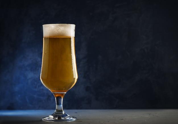 Стакан холодного светлого пива лагер на темном фоне