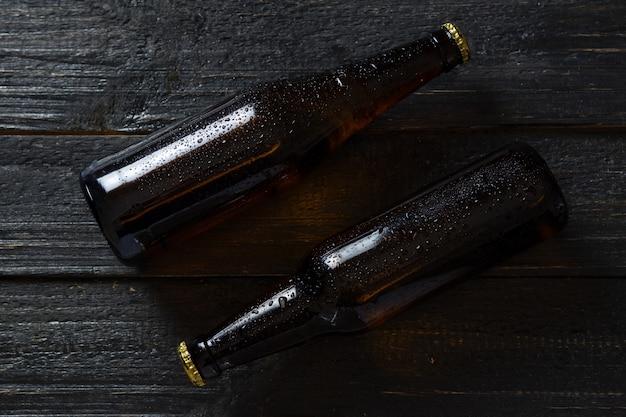 Две бутылки светлого пива на деревянном столе. капли на стекле