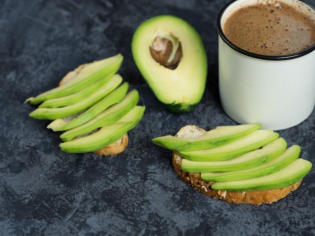 Нарезанный авокадо на тосте. чашка кофе