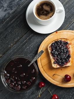 白いカップのコーヒーと黒いテーブルの上の白い皿にチェリージャムとトースト