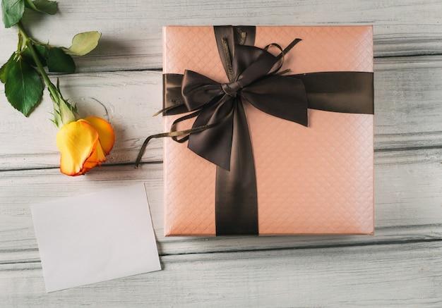 Красивый подарок в штучной упаковке на праздник и роза