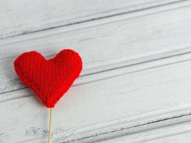 赤いハート愛のシンボルと木製の織り目加工の背景にバレンタインデーのコンセプト