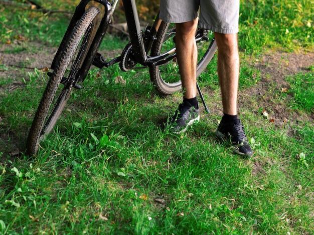 日没のクローズアップで緑の夏の森で自転車の横にあるサイクリスト