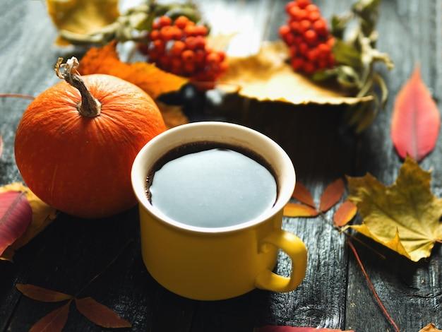 秋の背景。秋の葉とカボチャとエスプレッソのカップ。感謝祭