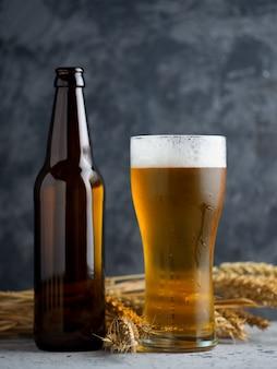 木製の背景に軽いビールとビール瓶のガラス