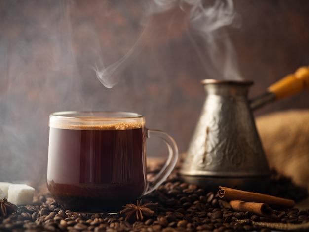 エスプレッソ透明ガラスカップとテーブルの上のコーヒー豆