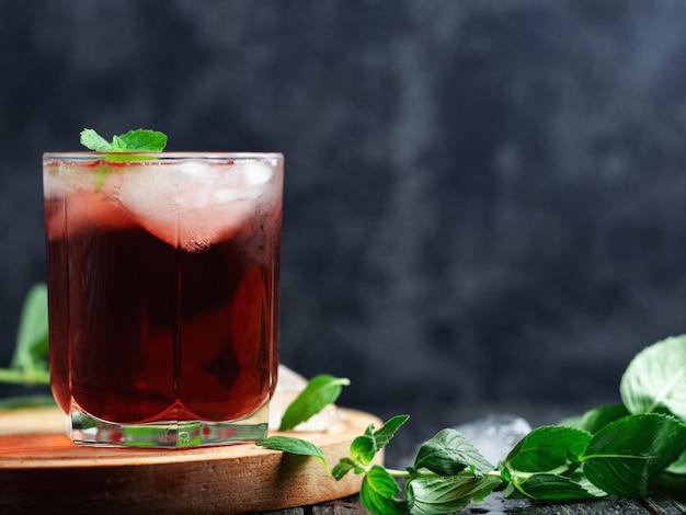 グラスに氷とミントの赤いアルコールカクテル