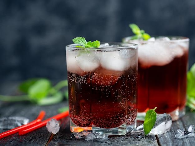 赤い夏の氷とミントのアルコールカクテル。ソーダなしおよびソーダあり