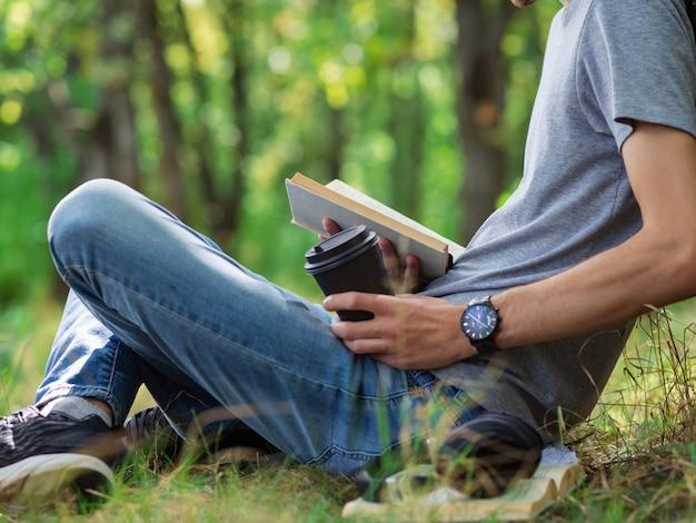 若い男の学生は本を読んで、公園の芝生の上に座って試験の準備をします。