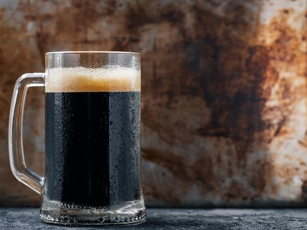 Кружка темного пива на деревенском темном фоне