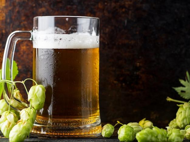 Кружка светлого прыгающего пива на темном ржавом фоне с зеленым хмелем