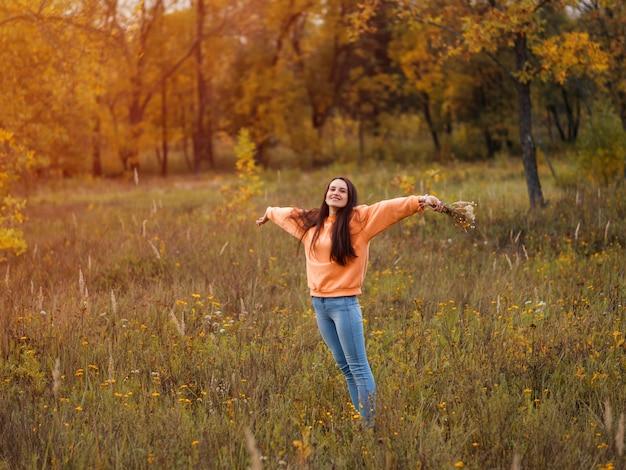 秋の森を歩くオレンジ色のパーカーで幸せな若い女性。ライフスタイル