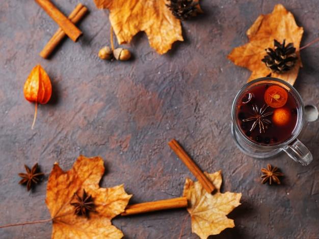 自家製の秋のホットワインとシナモン、スパイス、キンカン、コップのテーブルの上の秋の乾燥葉のガラス