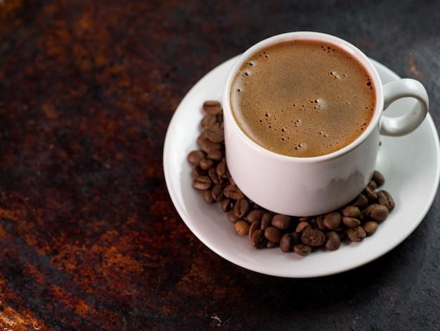 コーヒー豆とさびた鉄茶色の背景に白いエスプレッソコーヒーカップ
