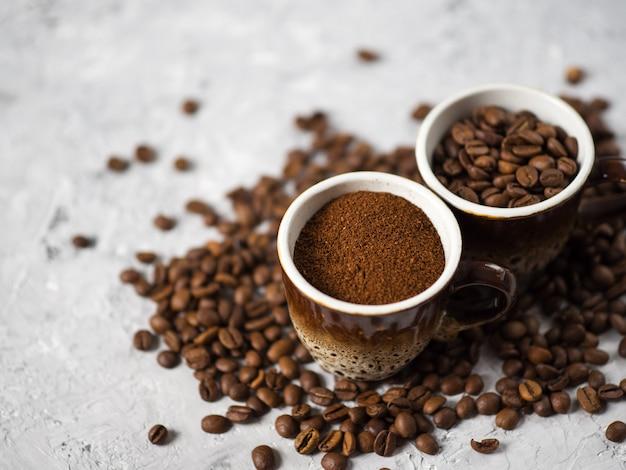 挽きたてのコーヒーと天然のコーヒー豆を入れたコーヒーカップ