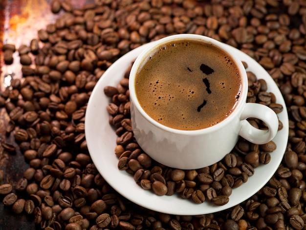 閉じる-コーヒー豆の白いコーヒーカップのクローズアップ-コーヒー豆の白いコーヒーカップのクローズアップ