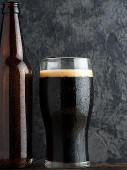 暗いテーブルの上にビール瓶とクラフトビールポーターの完全なガラス