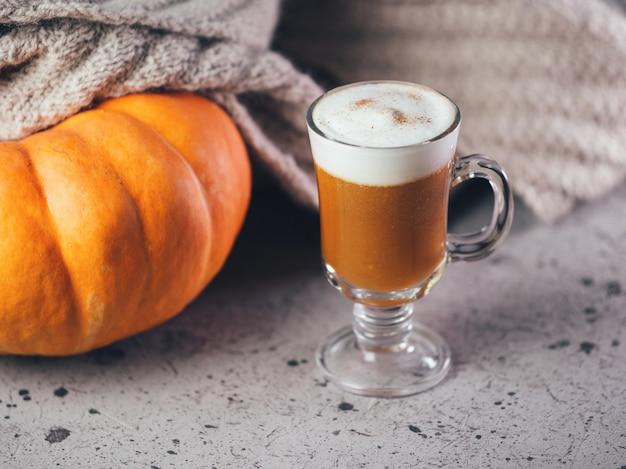 秋のカボチャラテガラス。グレーのテーブルに温かい飲み物とニットスカーフ。