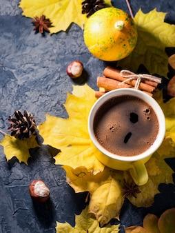 一杯のホットコーヒー、居心地の良い秋の朝、暗い石のテーブルトップビューにカラフルな秋のカエデの葉