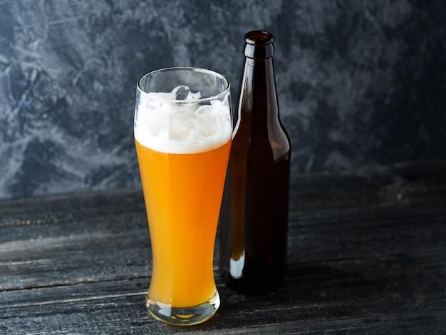 冷たい未濾過小麦ビールと暗闇の中でビール瓶のガラスのクローズアップ