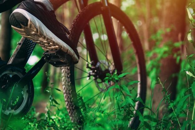 Велосипедист на горном велосипеде в лесу. крупным планом ноги на педали велосипеда. экстремальный вид спорта