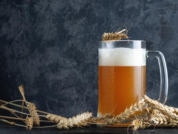 Стеклянная кружка пшеницы нефильтрованного пива на фоне бетонной стены в пабе с копией пространства