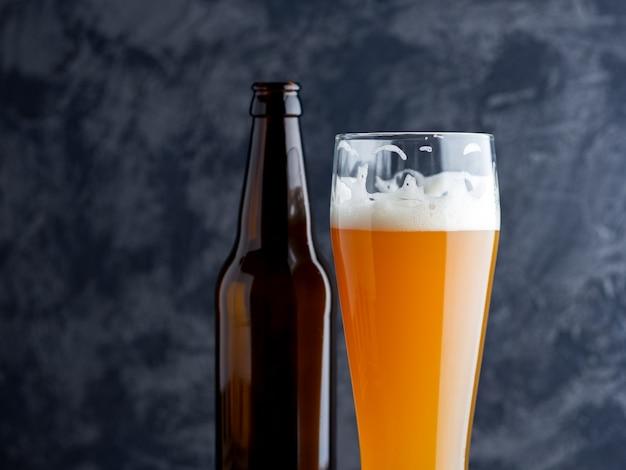 ガラスの冷たい未濾過小麦ビールとビール瓶のクローズアップ
