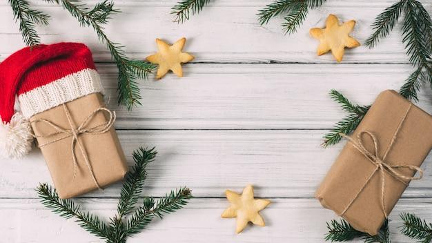 クリスマスツリーの枝とお菓子とクッキーのテーブルの上のクリスマスと新年の贈り物