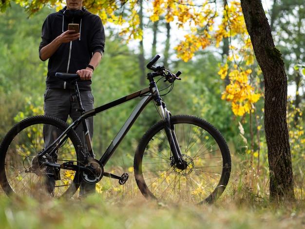 Парень велосипедист в осеннем лесу в октябре. активный образ жизни. активный отдых и велоспорт